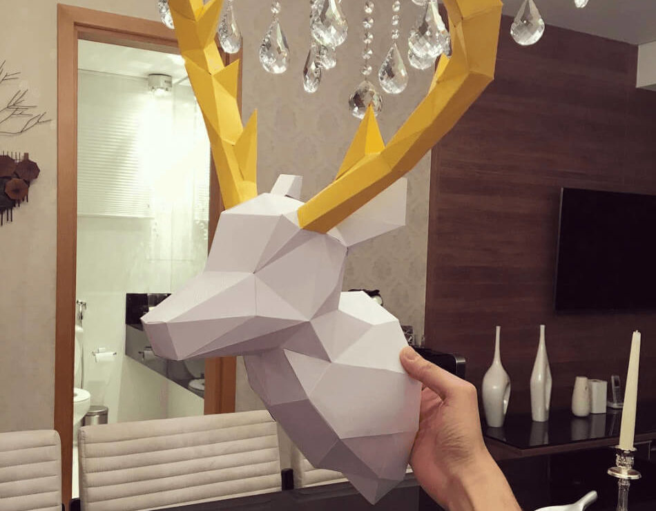 Cabeça de alce branco com chifre amarelo segurada por uma mão