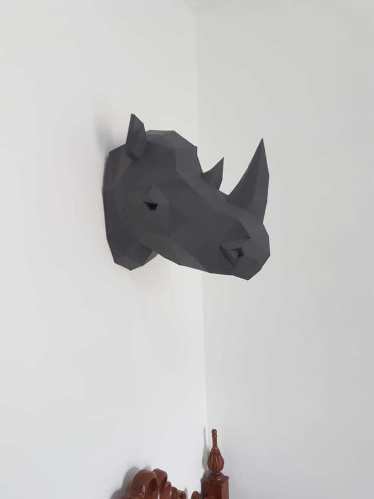 cabeça de rinoceronte na parede acima da cama